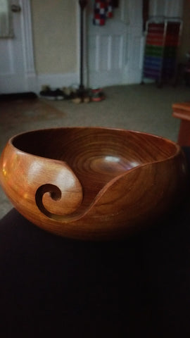 Wooden yarn bowl sitting on a dark table with beige floors and yellow walls in the background