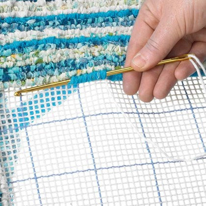 Woman's hand holding an aluminum gold locker hooking needle while working on a blue and white striped locker hooking rug project on a white background