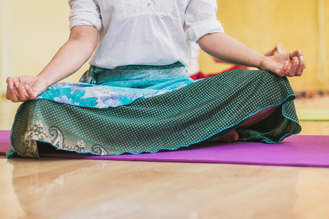 A person sitting in the lotus position, wearing a bright blue and teal sari skirt.