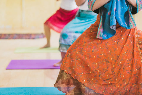 Three women, doing yoga on mats, in a line. The woman in front is wearing an orange skirt, the woman behind her is wearing a blue skirt, and the woman behind her is wearing a pink skirt.