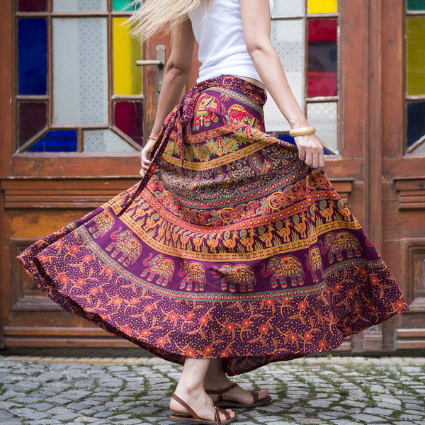 Woman standing in front of wooden double doors with stained glass windows, standing on paved sidewalk, and twirling wearing a multicolored cotton maxi wrap skirt