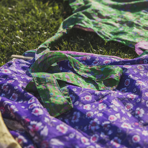 A floral purple skirt and a floral green skirt laying on the grass under the sun.