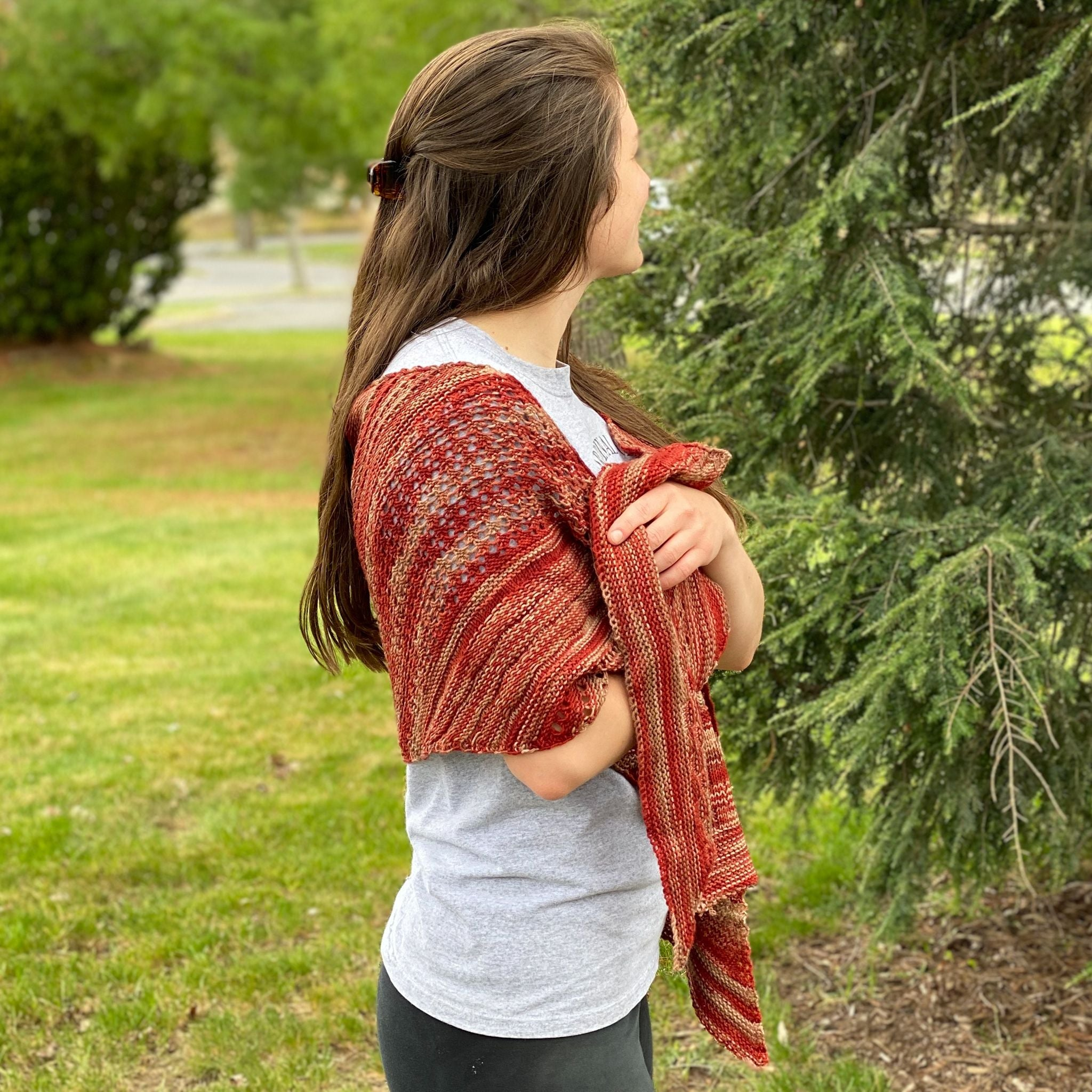 Brunette woman wearing maroon and orange madeleine shawl looking completely away from the camera in front of tree.