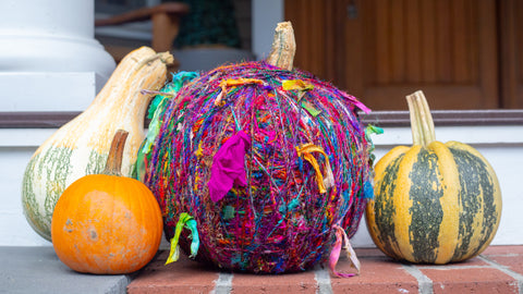 Yarn-wrapped pumpkin with three other gourds sitting on a front porch step