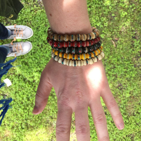 Woman's wrist wearing Handcrafted Himalayan Bracelets stacked, hovering over grass