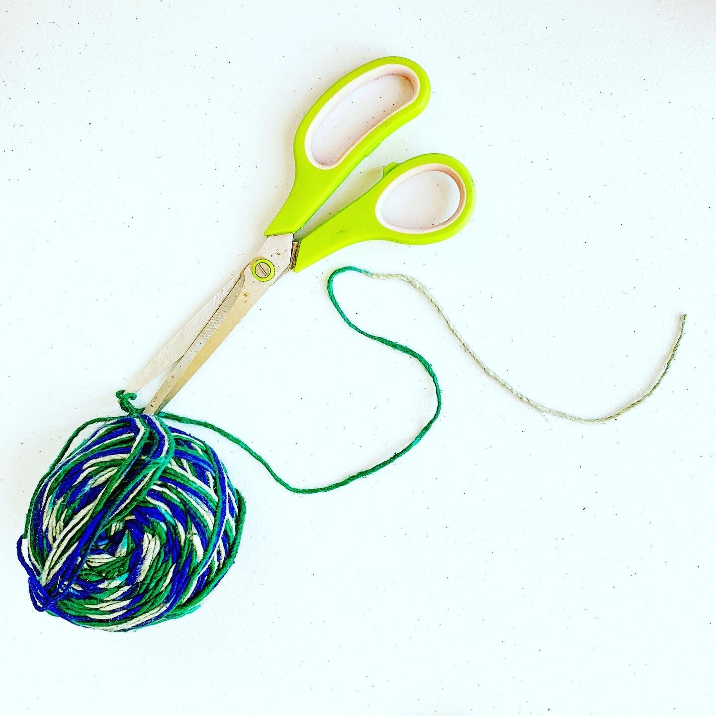 Photograph of a pair of green handled scissors preparing to cut blue green yarn.