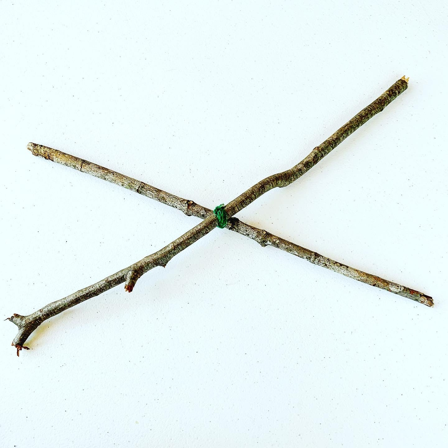 Photograph of two sticks overlapping each other to form a X tied together in the middle with blue-green yarn.