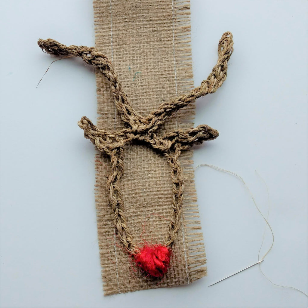 Crochet reindeer head attached to a burlap rectangle sitting on a white background