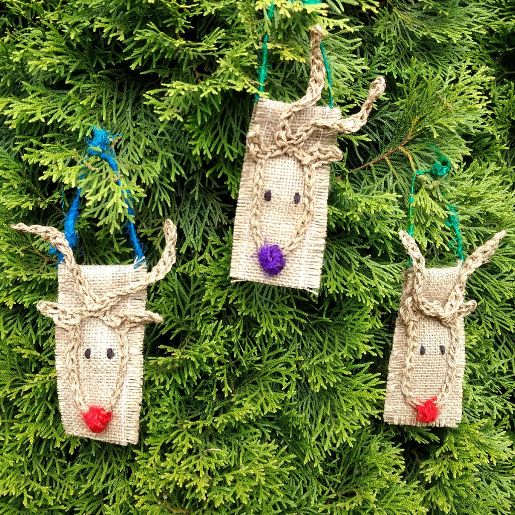 Three burlap crafted reindeer hanging on a green bush