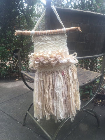 Small white woven wall hanging hung from a metal outdoor chair sitting on top of concrete in front of greenery