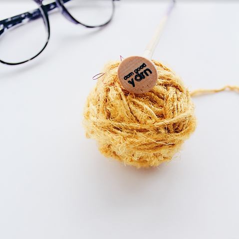 Wooden crochet hook with engraving that reads 'Darn Good Yarn' sitting next to a yellow yarn ball and a black pair of glasses on a white background