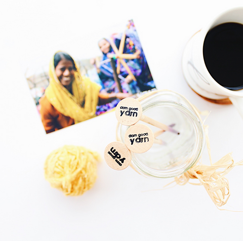 3 Wooden crochet hooks standing in a glass jar, a yellow ball of yarn, a white mug of coffee, and image of artisans, all sitting on a white background