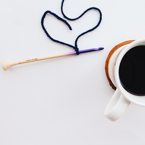 Purple wooden ombre crochet hook holding a navy blue crochet chain with a white mug of coffee sitting on a white background