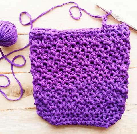 Partially made Violet Summer Tote with a yarn ball and crochet hook on a wooden background