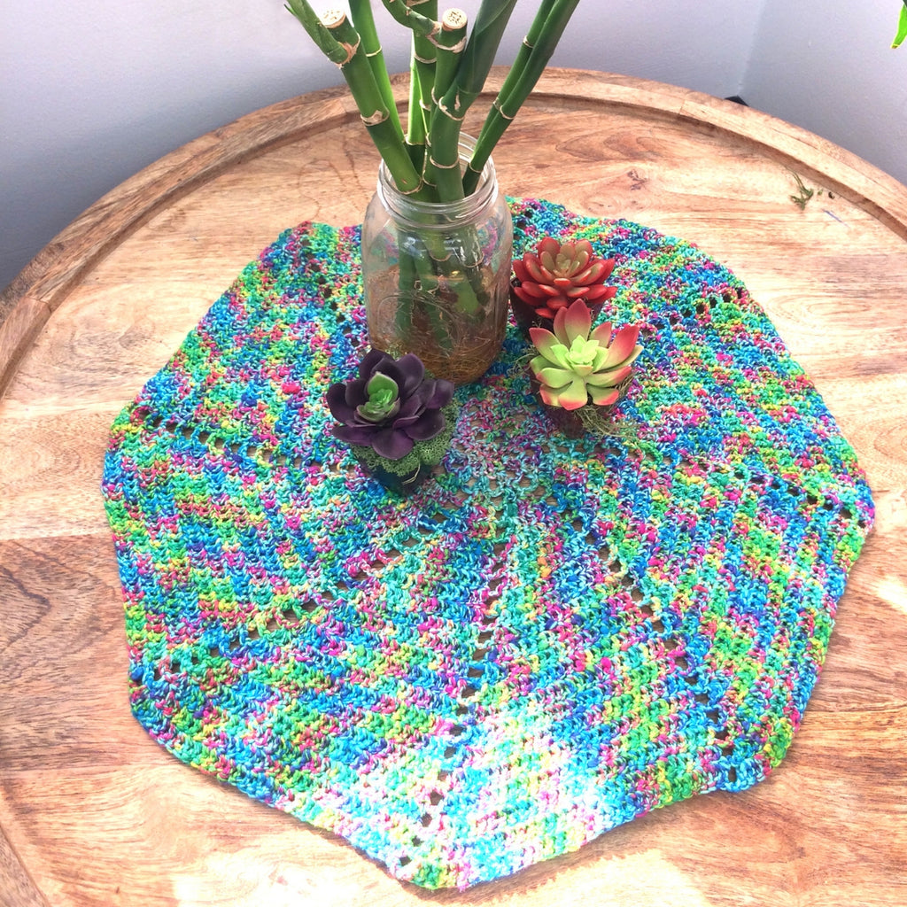 Multicolored spiral fan doily on a wooden table underneath 3 faux succulents and a glass vase full of greenery