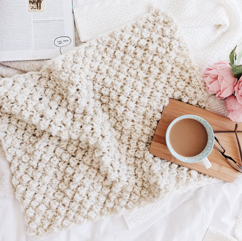 Raspberry Dreams Baby blanket sitting on a white bed with a wooden coaster, coffee mug, and pair of glasses