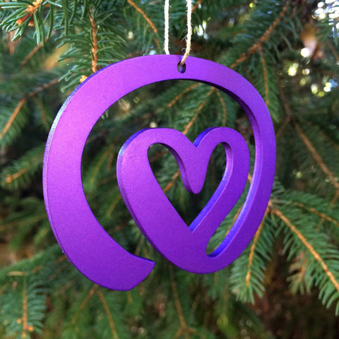 Purple heart-shaped Christmas Ornament hanging from a christmas tree