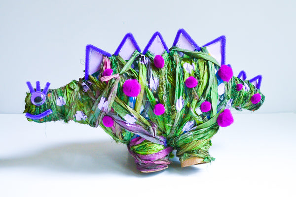 Partially made Yarn Wrapped Stegosaurus on a white background