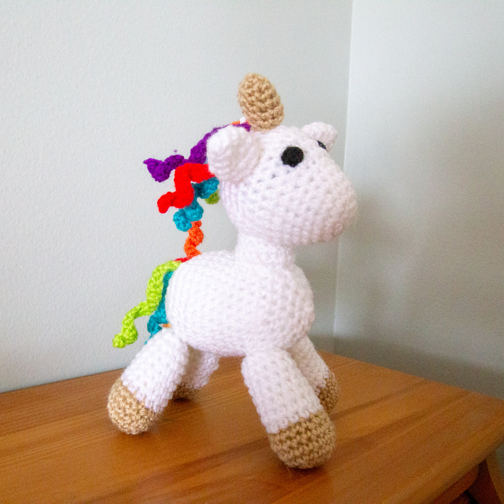 White unicorn amigurumi stuffed animal on a wooden surface next to a white wall