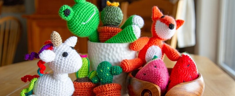 A frog, fox, unicorn, cacti, and watermelon amigurumi sitting in a yarn bowl.