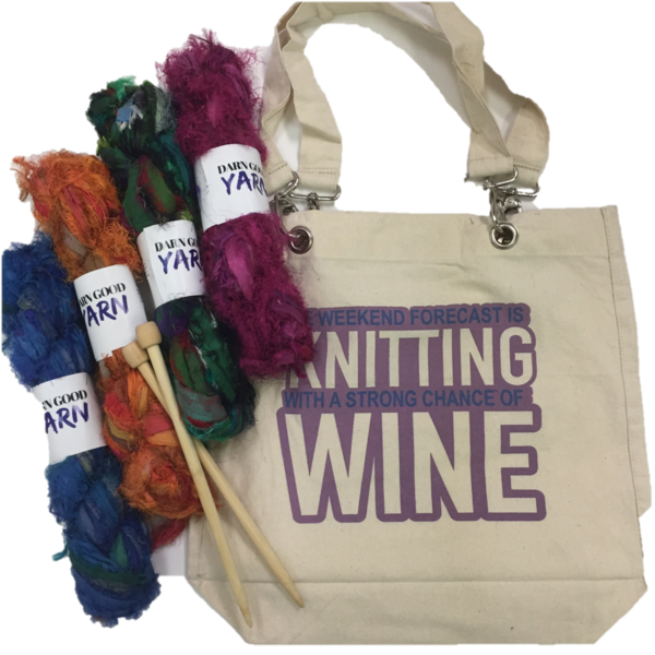 Beige tote bag with purple text that reads 'Weekend forecast is knitting with a strong chance of wine', 4 skeins of silk yarn in blue, orange, green, and purple, and wooden knitting needles all on a white background