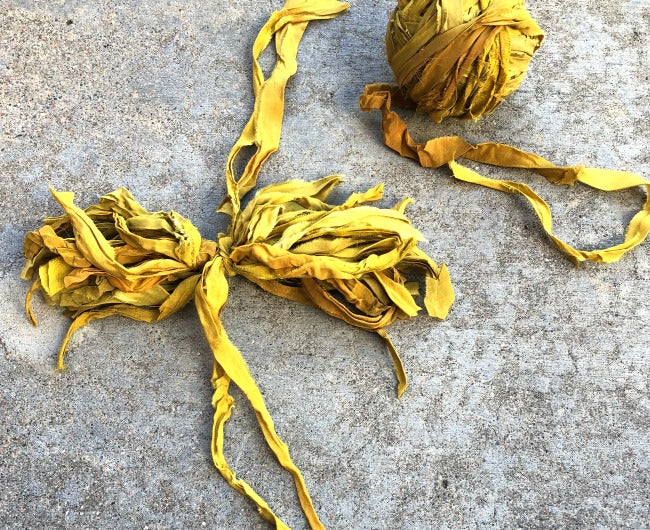 Yellow ribbon tied into a bow next to a yellow yarn ball sitting on a concrete surface