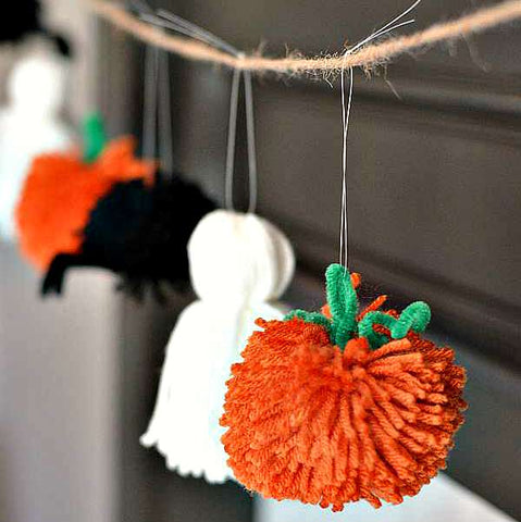 Pumpkin, ghost, and spider yarn garland hanging in front of a black wall