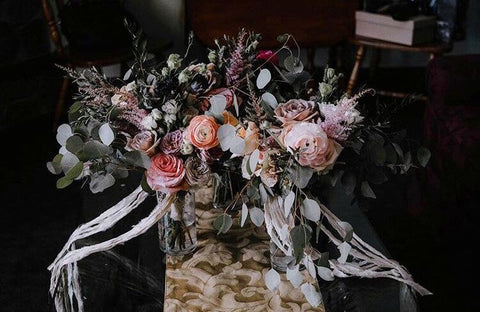 3 bouquets of wedding flowers tied together with recycled sari silk ribbon, sitting on a wooden tabletop