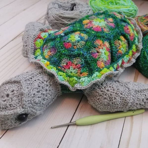 Crochet Amigurumi stuffed animal Turtle sitting on a wooden surface with a beige plastic crochet hook