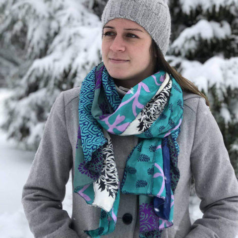 Close up of woman wearing a winter coat and sari silk medley scarf while standing in snow
