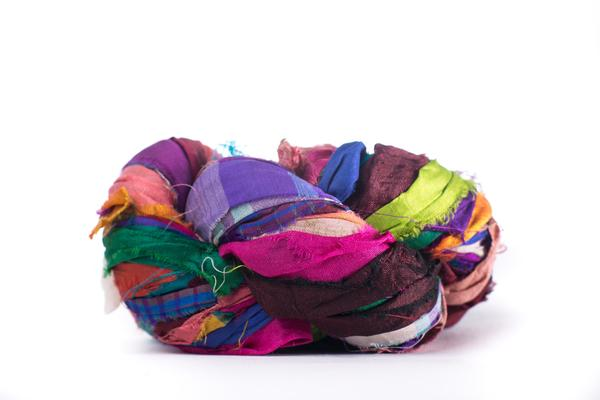 Multicolored skein of sari silk ribbon yarn on a white background
