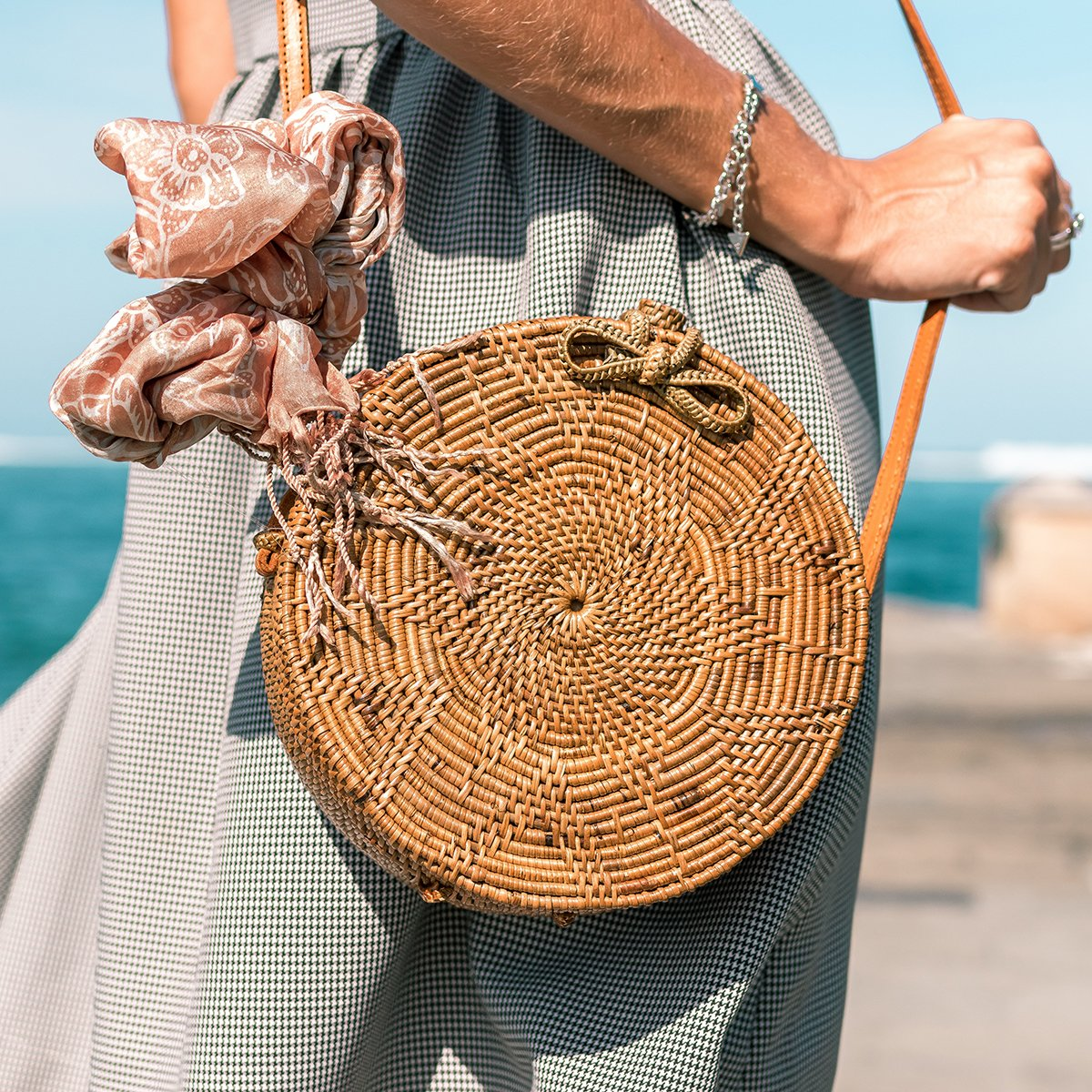 Close up of woman holding a basket bag with a pink silk scarf tied to the handle and wearing a green houndstooth dress on a beach