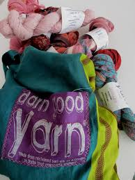 Several skeins of pink yarn sitting next to a teal and green silk tote on a white background