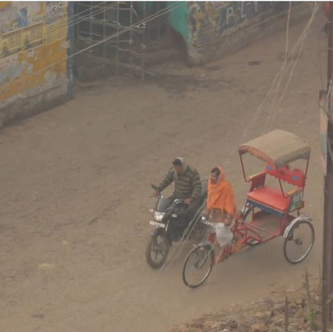Two people are driving down a murky, dirt covered street in India. A man is on a black motorcycle, driving beside a woman in an orange sari. The woman is riding a bicycle with a small riding cab attached to the back of her bike. The cab is empty.