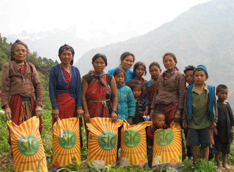 Multiple Women and children holding large yellow bags and standing amongst greenery