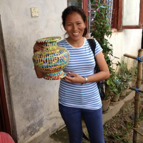 Beni, our incredible partner, is smiling while presenting one of the woven vases made out of recycled materials that her team creates.