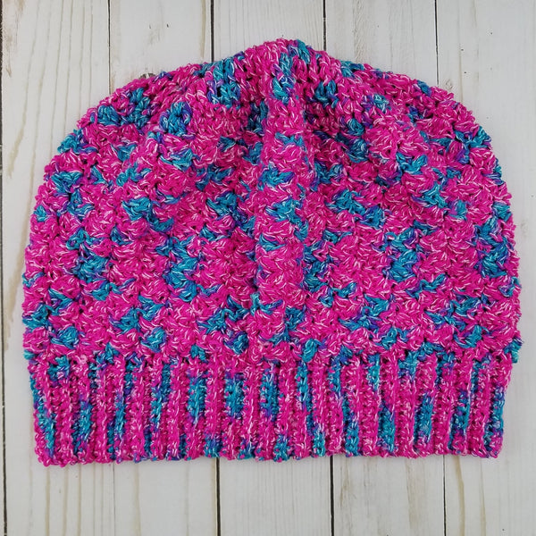 Pink and blue beanie on a wooden background