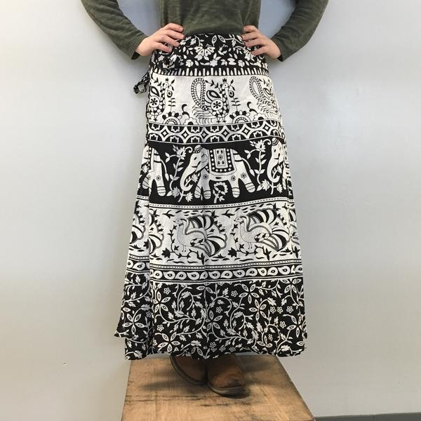 Close up of woman wearing a black and white patterned maxi skirt with black tights and brown boots in front of a white background