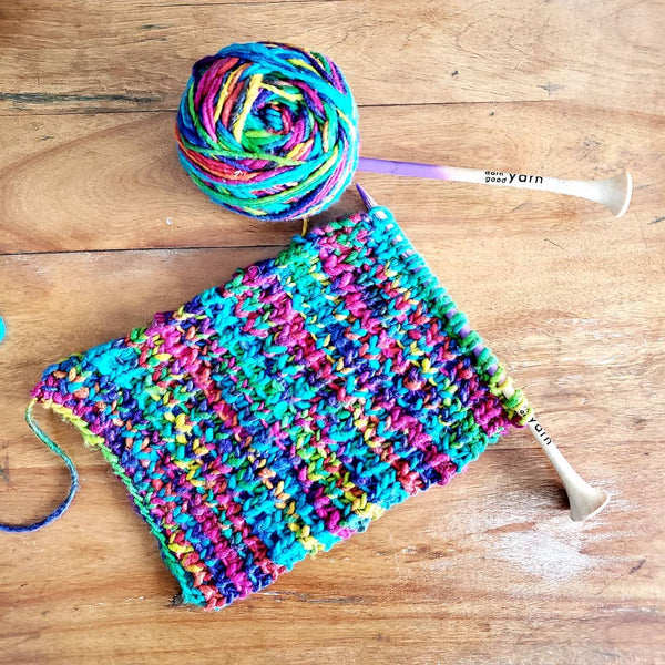 Water Color Yarn knitting project on a wooden surface