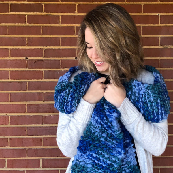 Woman wearing the Blue Ridge Blanket Scarf in front of a brick wall