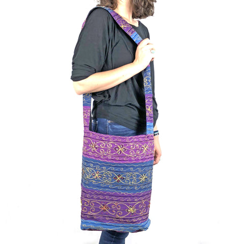Woman wearing black and holding the boho sling crossbody bag on her shoulder and standing in front of a white background