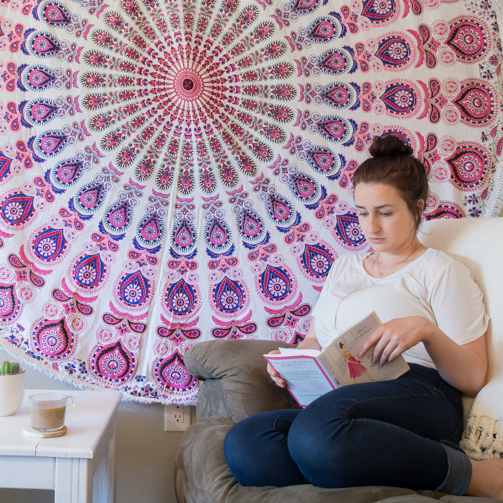 Woman sitting on a beige couch in front of a pink, purple, and white mandala tapestry hanging on the wall