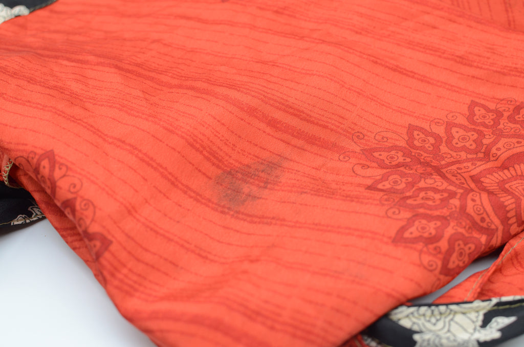Close up of a red sari wrap skirt folded on a white background with a small dark stain on the fabric