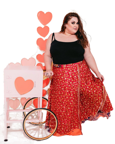 Woman standing next to rolling cart with heart background dressed in a red sari wrap skirt and black tank top.