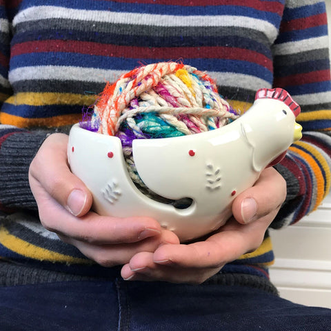 Close up of woman wearing a striped sweater and holding a rooster-shaped Ceramic Yarn Bowl in both hands