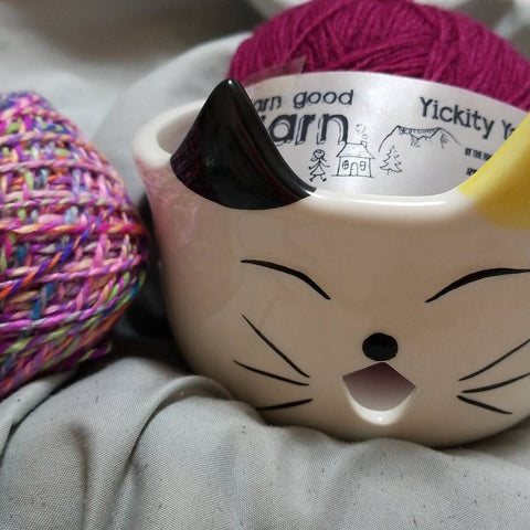 Cat-illustrated Ceramic Yarn Bowl sitting on a gray surface with two multicolored balls of yarn