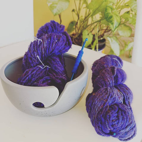 White Ceramic Yarn Bowl with two purple skeins of yarn and a crochet hook, sitting on a wooden surface