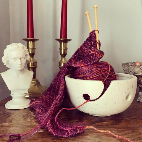 White Ceramic Yarn Bowl holding a pink ball of yarn, wooden knitting needles, and a matching crochet project, sitting on a wooden surface next to a ceramic bust and two gold candle holders