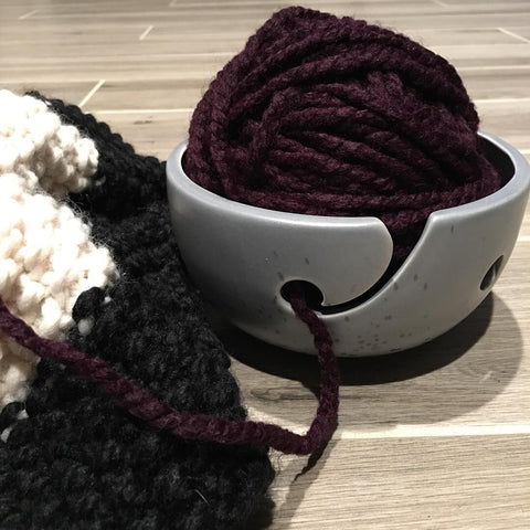 Ceramic Yarn Bowl holding a purple ball of yarn, sitting on a wooden surface next to a gray and cream-colored crochet project