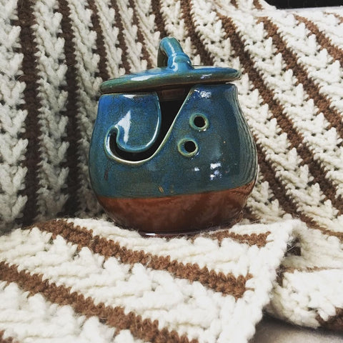 blue Ceramic Yarn Bowl sitting on a cream and brown striped crochet blanket